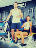 Smiling young man and woman taking pause between exercising in g Stock Photography