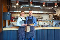 Smiling young man and woman using tablet at small eatery restaurant royalty free stock photo