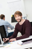 Smiling young man at work in the office Stock Image