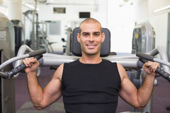 Smiling young man working on fitness machine at gym Royalty Free Stock Photo