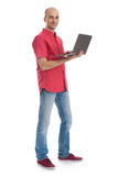 Smiling young man working on his laptop Stock Photography