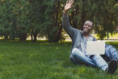 Smiling man working on laptop on grass. Smiling young man working on laptop, sitting in park on grass and greeting someone. Technology, communication, education royalty free stock image
