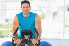 Smiling young man working out at spinning class Stock Photo