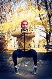 Smiling young man working squats at park. Royalty Free Stock Images