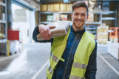 Smiling young man working in a warehouse. Standing with a bag of product over his shoulder grinning happily at the camera, close up view Royalty Free Stock Photos