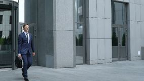 Smiling young manager leaving office building, successful project, promotion. Stock footage stock footage