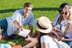 Young man giving blank notebook to girl in straw hat while laughing friends sitting on green grass. Smiling young men giving blank notebook to girl in straw hat Royalty Free Stock Photos