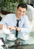 Smiling young men pours tea into a cup. Beautiful smile. Coffee time Royalty Free Stock Photos