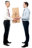 Smiling young men receive cartons boxes Stock Photography