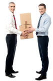 Smiling young men receive cartons boxes Stock Images