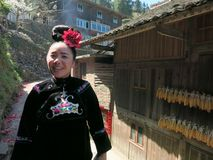 A smiling young miao woman walking in the village street royalty free stock photo