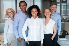 Smiling young african leader looking at camera with diverse team stock image