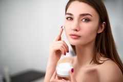Smiling young mixed race woman applying face cream on her perfect skin. Model with flawless skin holding white jar of royalty free stock photos