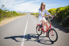 Smiling young model posing while riding bike Stock Images