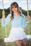 Smiling young model relaxing sitting on swing Stock Images