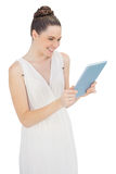 Smiling young model in white dress holding tablet pc Royalty Free Stock Photography