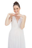 Smiling young model in white dress posing Royalty Free Stock Image