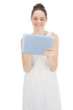 Smiling young model in white dress using tablet computer Stock Photo