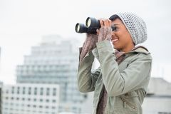 Smiling young model in winter clothes watching with binoculars Stock Photography