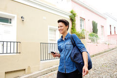 Smiling young modern woman walking with bag and cell phone Stock Photo