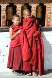 Smiling young monks standing by the religious prayer wheels at Paro Rinpung dzong, Paro, Bhutan