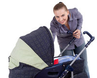 Smiling young mother with baby buggy Stock Photos