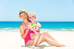 Smiling young mother and child on beach showing starfish Stock Photos