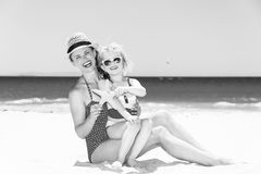 Smiling young mother and child on beach showing starfish Royalty Free Stock Images