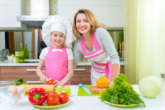Smiling young mother with daughter cooking. Royalty Free Stock Photos