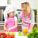 Smiling young mother with daughter cooking. royalty free stock images