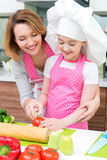 Smiling young mother with daughter cooking. Stock Image