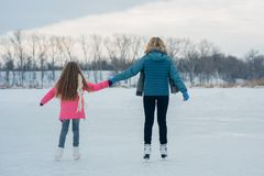 Young family have fun on the ice area in a snowy park royalty free stock photo
