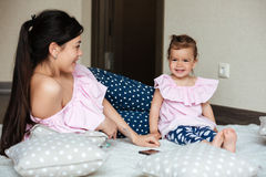 Smiling young mother with her little daughter lies on bed Stock Photos