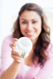 Smiling young mother holding a feeding-bottle Stock Photo