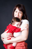 Smiling young mother holding her baby daughter Stock Image