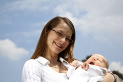 Smiling young mother holding her yawning daughter Royalty Free Stock Images