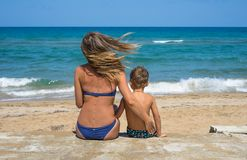 Smiling young mother kisses baby near the sea. Happy summer days. Boy woman royalty free stock image