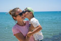 Smiling young mother kisses baby near the sea. Happy summer days. Smiling and happy mother and her son playing and running on the beach. Concept of friendly royalty free stock photography