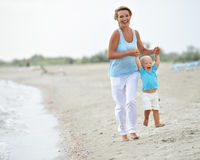 Smiling young mother with little child running. Royalty Free Stock Images