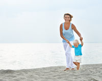 Smiling young mother with little child running. Royalty Free Stock Image