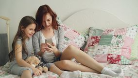 Smiling young mother with little cute daughter watching social media photos on smartphone using touchscreen and have fun. While sitting in bright bedroom at stock video footage