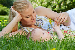 Smiling mother reclines on green grass next to her baby Royalty Free Stock Images