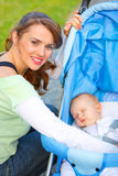 Smiling young mother taking care about her baby. Smiling young mother sitting near stroller and taking care about her baby Stock Image