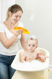Smiling young mother washing her baby`s head with shampoo Stock Photos