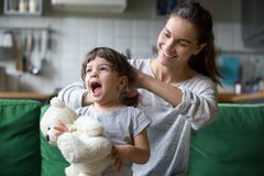 Smiling young mum making ponytail to little daughter. Smiling young loving mum making ponytail to little preschool laughing daughter with toy sitting on sofa royalty free stock images
