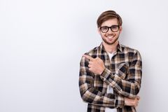 Smiling young nerdy bearded stylish student is standing on pure. Background in glasses and casual outfit, pointing on the copyspace royalty free stock photos