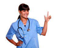 Smiling young nurse looking at you pointing up Stock Photography