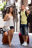 Smiling young pair with luggage walking in city Stock Photo