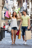 Smiling  young pair with shopping bags at city Stock Image