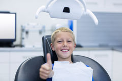 Smiling young patient sitting on dentist chair Royalty Free Stock Photography